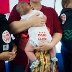 Babies with 'paid family leave' stickers