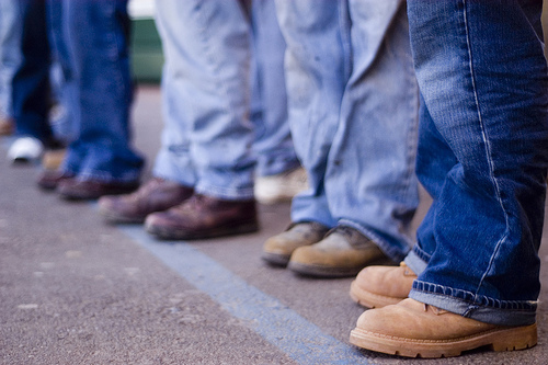 group of people from the knees down wearing jeans and boots