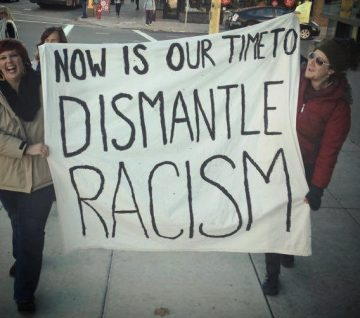 two people walking and holding a large sign that reads: now is our time to dismantle racism