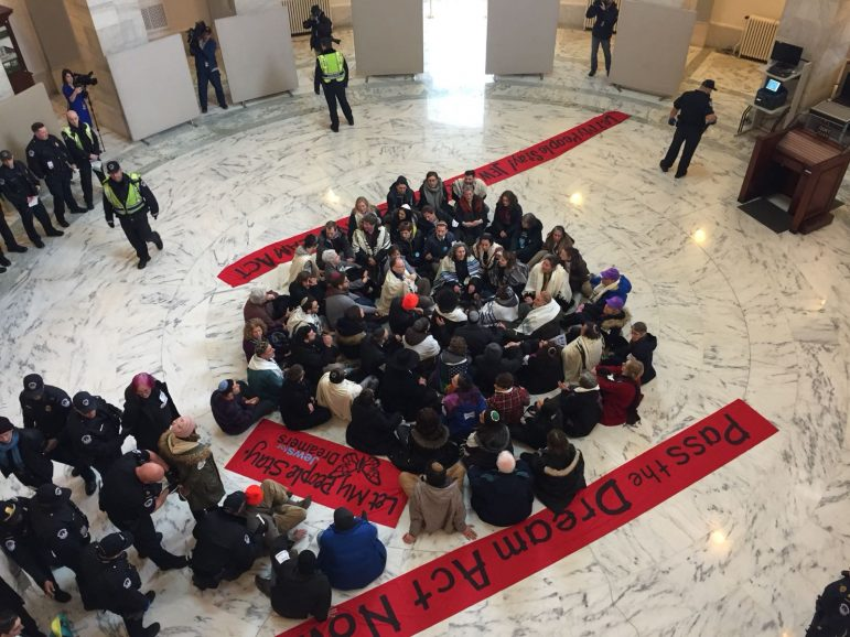 """people participating in a sit-in in the Maryland rotunda with signs that say """"pass the dreamer act now"""""""