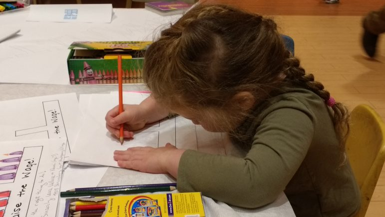 a child drawing on a piece of paper