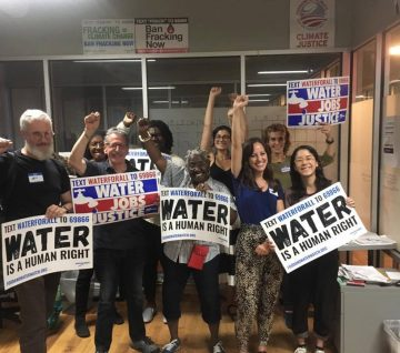a group of people holding signs advocating that water is a human right