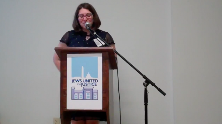 Person speaking at a podium with a JUFJ sign on it