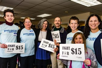 """JUFJ leaders pose with signs that read """"Fight for $15"""""""