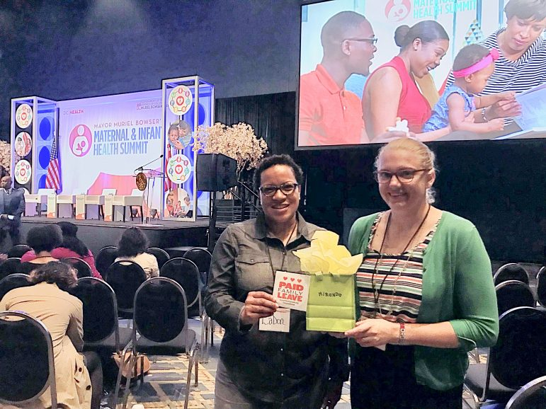 two people at the Maternal & Infant Health Summit holding a gift bag and a sticker that has the paid family leave logo
