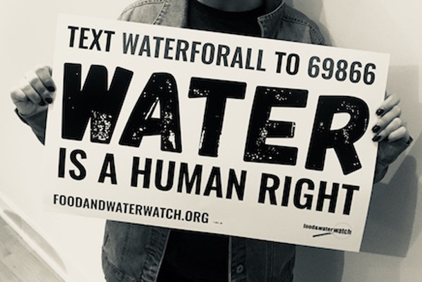 A person is holding a sign hat reads: Text WATERFORALL to 69866; water is a human right; foodandwaterwatch.org