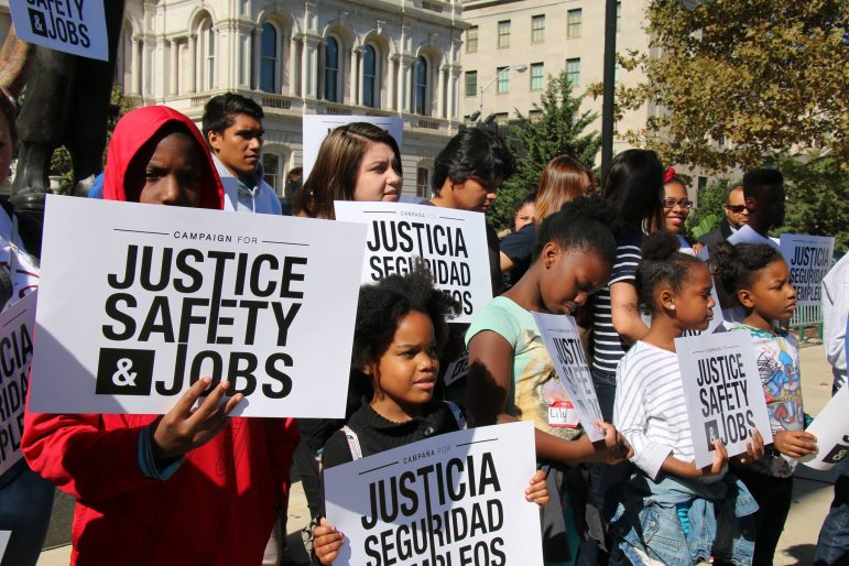 activists holding signs that say justice safety and jobs
