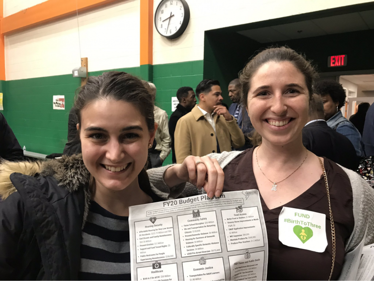 smiling young women hold a FY20 budget plan