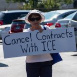 """woman holds sign reading """"cancel contracts with ice"""""""