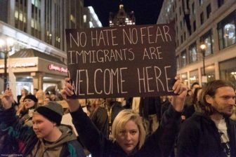"""protester holding sign reading """"no hate no fear immigrants are welcome here"""""""
