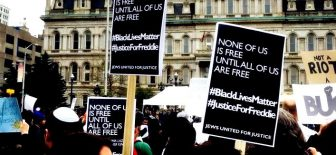 Signs: None of us is free until all of us are free. #BlackLivesMatter #JusticeForFreddie