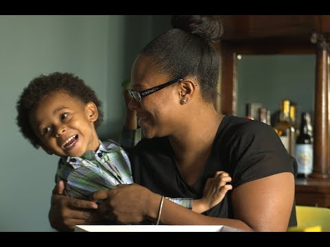 smiling woman holding a smiling toddler