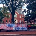 Two people hold a banner outside the Governor's mansion: Governor Hogan, Rent is Due. Cancel the Rent.