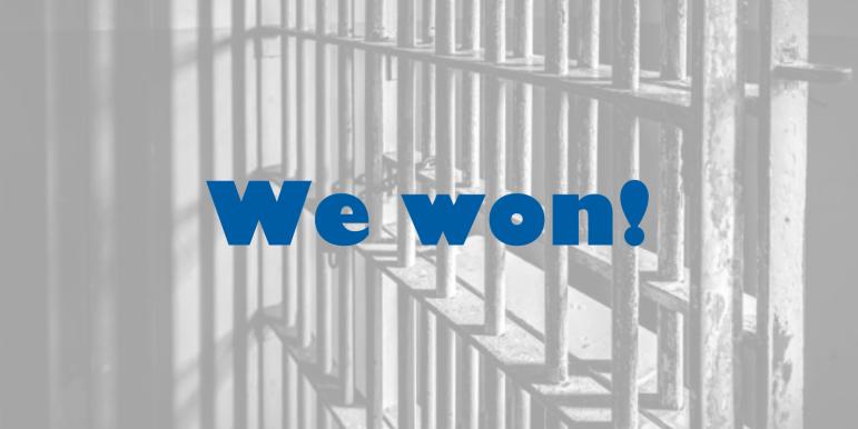 Jail bars with text overlaid: We won!